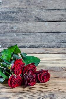 Bei fiori di rosa sulla tavola di legno, design rustico