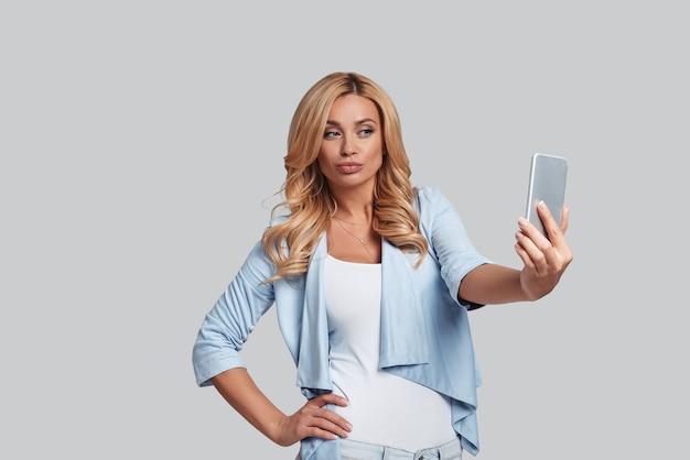 Selfie adorabile. attraente giovane donna che tiene la mano sul fianco e si fa selfie in piedi su sfondo grigio gray