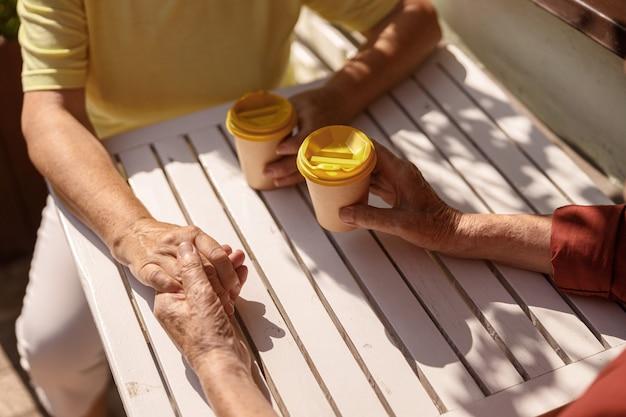 Una bella coppia di anziani si unisce per mano seduta al tavolino in un caffè di strada