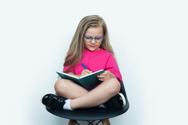Piccola ragazza bionda adorabile con gli occhiali che scrivono qualcosa in un libro