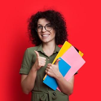 Bella studentessa con i capelli ricci e gli occhiali in possesso di alcuni libri e gesticolando il segno simile su un muro rosso con spazio libero