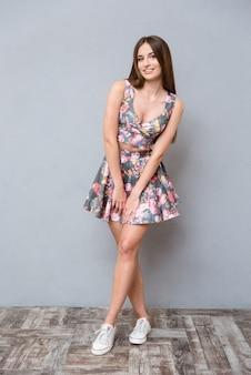 Bella dolce carina ragazza sorridente abbastanza felice con i capelli lunghi in abito estivo floreale in posa sul muro grigio