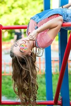 Bella ragazza adolescente in tuta di jeans con lecca-lecca appesi a testa in giù