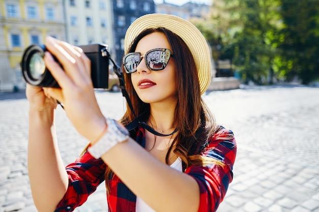 Bella ragazza turistica con capelli castani che indossa un cappello e camicia rossa, facendo foto con la fotocamera a sfondo vecchia città europea e sorridente, viaggiando.