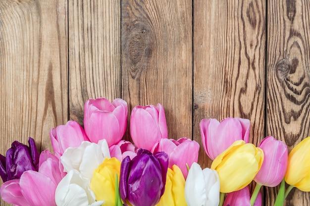 Bei fiori del tulipano sulla tavola di legno, design rustico