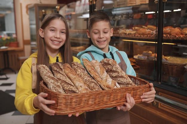Fratello e sorella gemelli adorabili che tengono il cestino del pane, lavorando al negozio di panetteria dei genitori