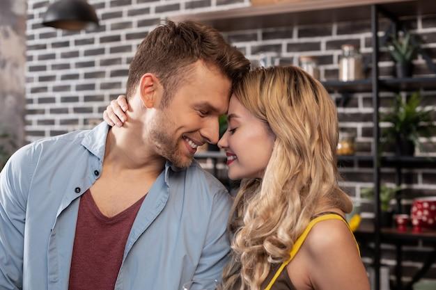 Bella donna. marito barbuto e allegro che sorride ampiamente mentre trascorre del tempo con la sua adorabile donna