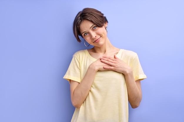 Bella donna che si tiene per mano sul petto sentendo grazie gratitudine reagendo in modo carino a qualcosa in casual ...