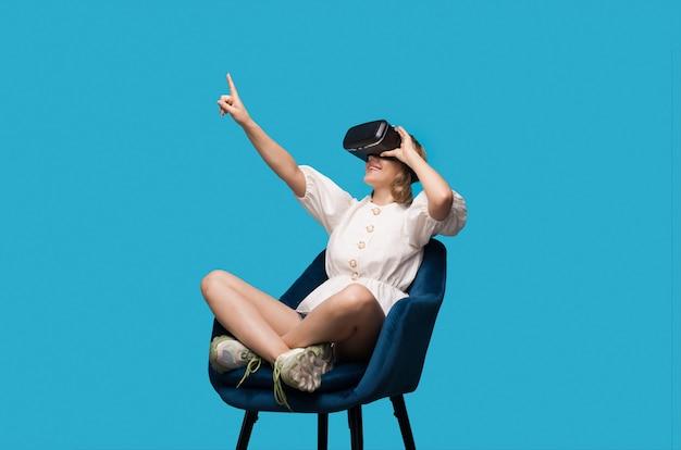 Bella donna seduta in poltrona sta indicando lo spazio libero durante il test di un auricolare vr su una parete blu