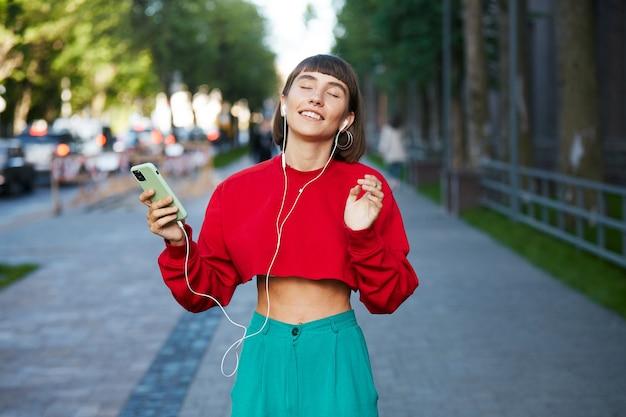 Bella donna in piedi sulla strada con gli auricolari e ascolta musica, donna millenaria carina in maglione rosso alla moda che tiene smartphone e musica d'ascolto