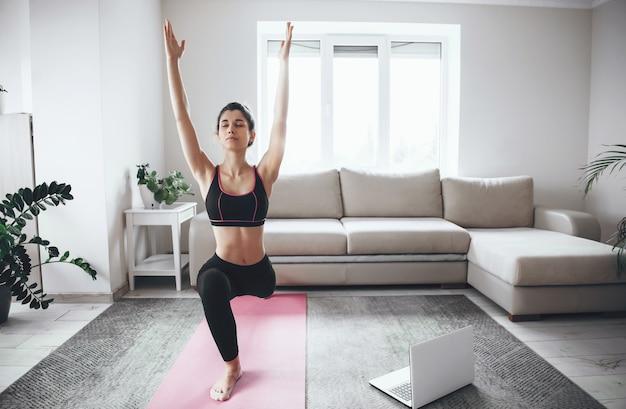 Bella donna che allunga i suoi muscoli prima della lezione di yoga a casa durante la quarantena con un laptop