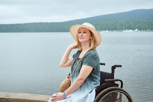 Bella donna in sedia a rotelle con cappello che si gode la vista sul mare o sul lago.