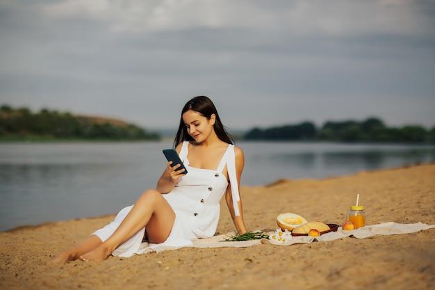 Bella donna in un vestito bianco che si siede con lo smartphone sulla sabbia in riva al fiume.