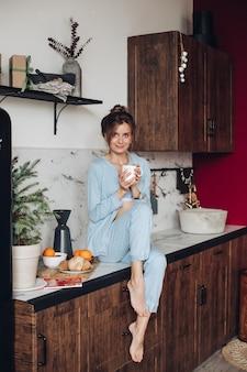 Bella donna con caffè in cucina. mattina di natale