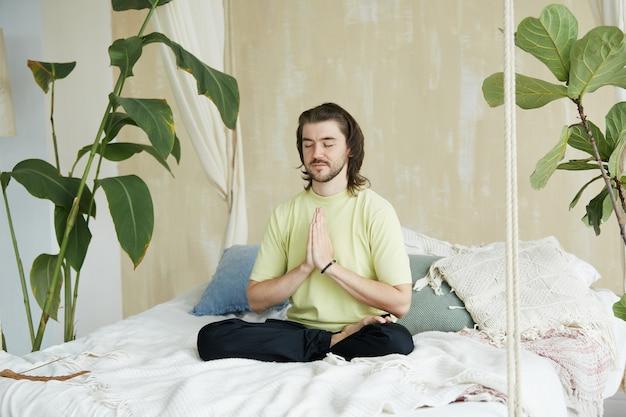 Insegnante di yoga adorabile che tiene namaste mudra seduto nella posa del loto, meditatore bello che pratica la meditazione a casa seduto sul letto in asana di yoga