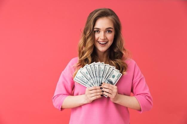Bella giovane donna bionda in piedi isolata sul muro rosa, mostrando banconote in denaro