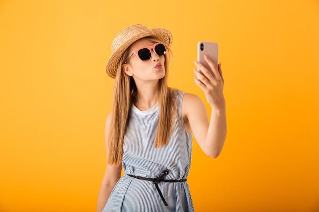 Bella giovane donna bionda in cappello estivo