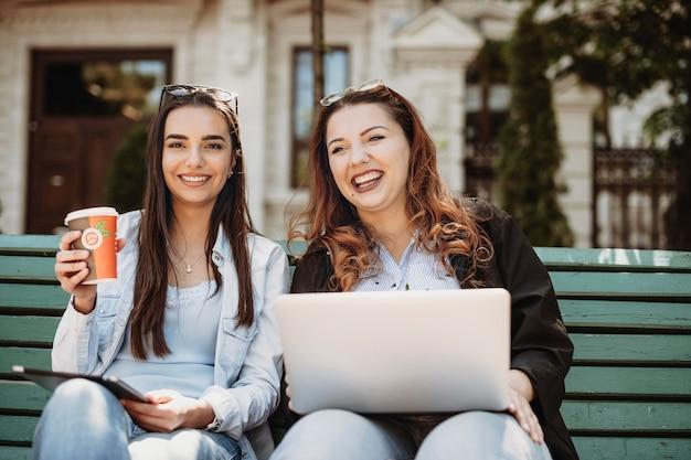 Bella giovane brunetta caucasica che tiene una tazza di caffè che ride mentre la sua amica sta tenendo un laptop e distoglie lo sguardo.
