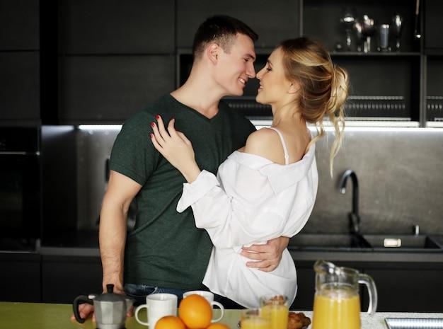 Bella giovane coppia in piedi e abbracciando su una cucina a casa