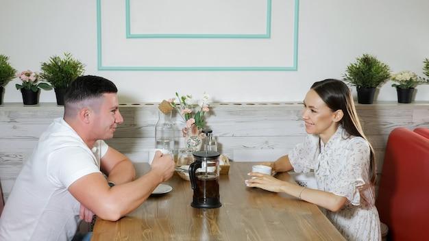 Una giovane coppia adorabile parla sorridendo e beve il tè seduti al tavolo di legno servito in un confortevole ristorante durante la data