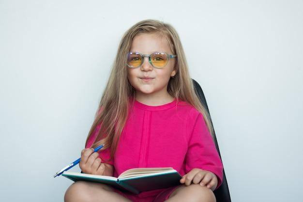 Bella ragazza giovane indossa occhiali e disegna qualcosa mentre sorride alla telecamera su una parete bianca dello studio