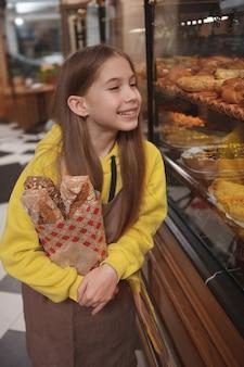 Bella ragazza che indossa il grembiule, tenendo il pane fresco, lavorando al caffè dei suoi genitori