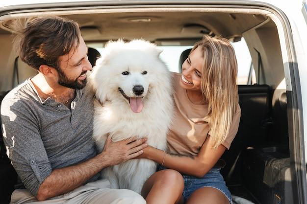 Bella giovane coppia felice seduta nella parte posteriore della loro auto in spiaggia, giocando con il cane