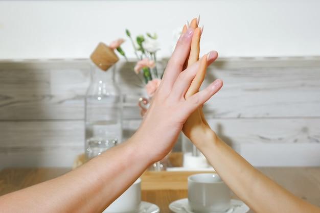 Un giovane adorabile e una ragazza dai capelli lunghi si toccano le mani con un appuntamento romantico al tavolo di legno in un accogliente ristorante in primo piano