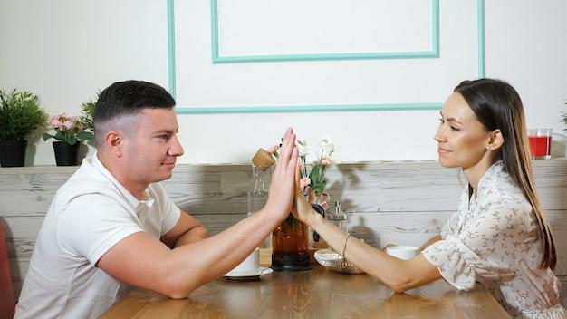 Un giovane adorabile e una ragazza dai capelli lunghi si toccano le mani con un appuntamento romantico al tavolo di legno in un accogliente ristorante