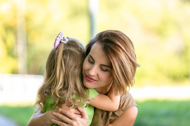 Giovani mamma e figlia adorabili nel caldo giorno di estate soleggiato. piccola figlia della madre e del bambino della famiglia felice che abbraccia e che cammina nel parco e che gode della bella natura.