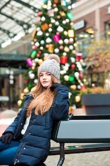 Bella giovane donna dai capelli rossi che indossa abiti invernali, in posa sullo sfondo di un abete natalizio