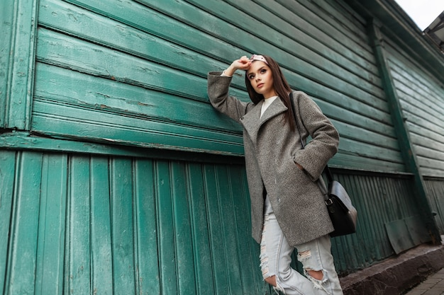Bella giovane donna in bandana alla moda in cappotto vintage in jeans strappati con borsa in pelle posa vicino a edificio verde da assi. attraente ragazza graziosa affascinante in abiti alla moda all'aperto.