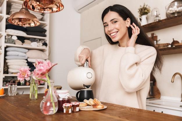Bella giovane donna con una tazza di caffè in cucina, utilizzando la macchina per il caffè