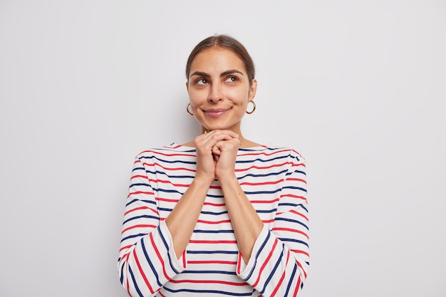 La giovane donna adorabile tiene le mani sotto il mento sorride guarda delicatamente sopra gli sguardi con ammirazione indossa un maglione a righe casual isolato sul muro bianco pensa a qualcosa di bello