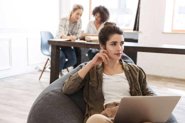 Bella giovane donna utilizzando il computer portatile mentre è seduto al chiuso, seduto in poltrona