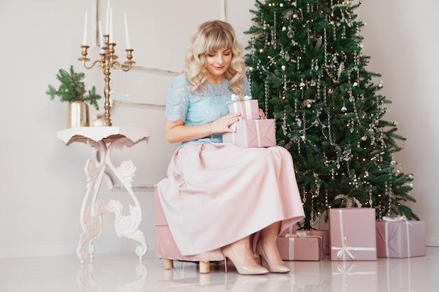 Bella giovane donna con uno stile elegante seduto al coperto vicino all'albero decorato con regali di natale rosa