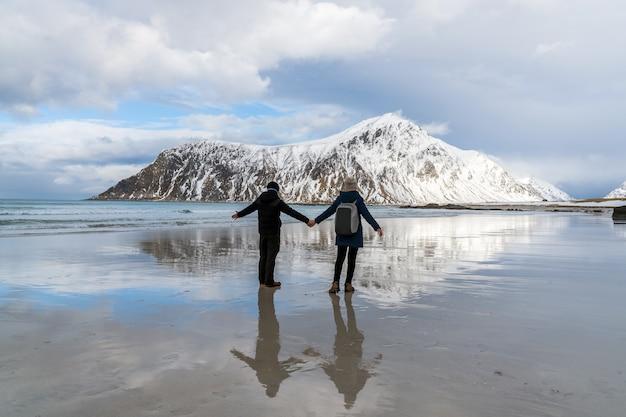 L'amante che si leva in piedi sopra la spiaggia di skagsanden in lofoten, norvegia.