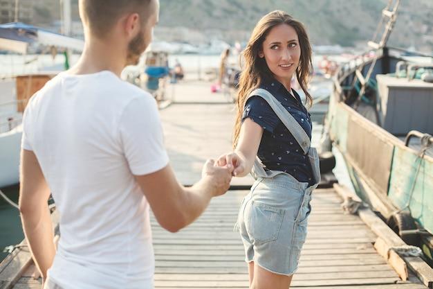 Gli amanti, ragazzo e ragazza, camminano su un molo di legno e si tengono per mano.