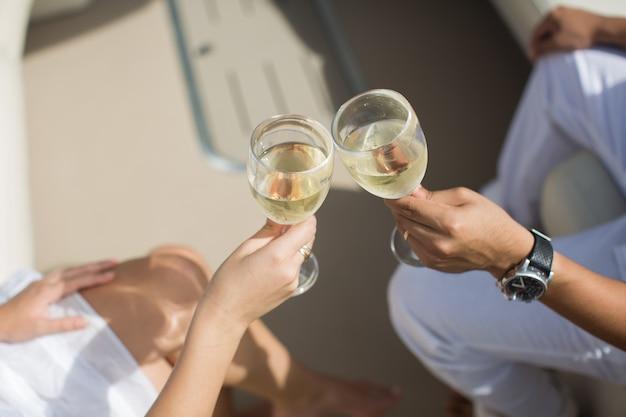 Gli innamorati celebrano la loro luna di miele su uno yacht. bicchieri di tintinnio della coppia appena sposata con champagne