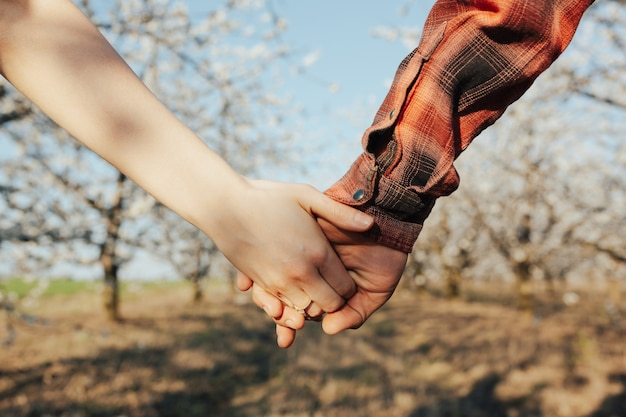 Coppia di amanti che tengono le mani in un giardino fiorito primaverile. anello al dito della ragazza, fidanzamento.