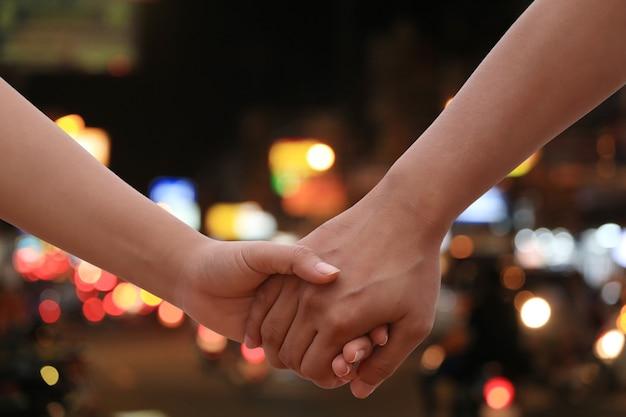 Amanti mano nella mano, coppie che si tengono per mano sulle luci notturne sullo sfondo della città per il design in incontri e concetto di viaggio.