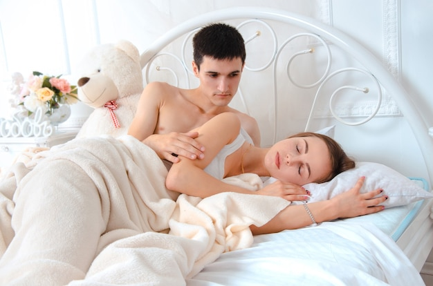Amanti sdraiati sul letto bianco. uomo che guarda la sua ragazza mentre dorme
