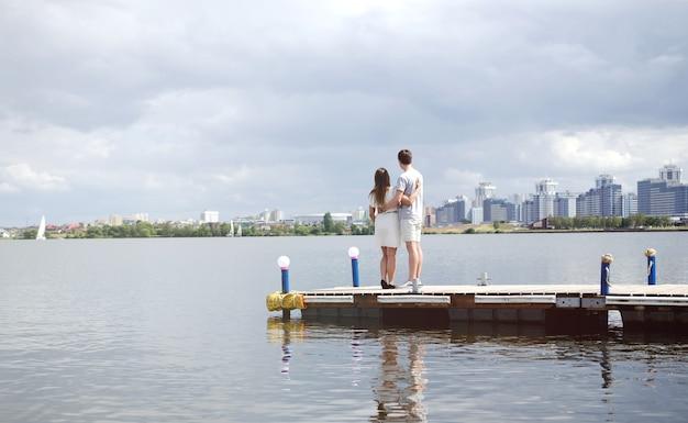Gli innamorati stanno sul molo e guardano il lago e la città, gli innamorati si rilassano