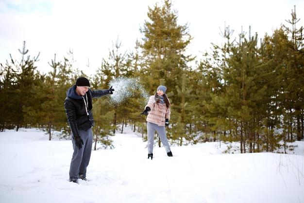 Gli amanti si lanciano la neve l'un l'altro giocando felici e allegri