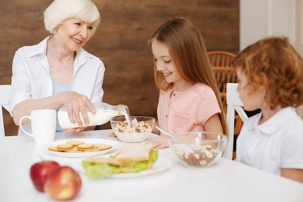 Amorevole e attenta donna anziana che prepara una colazione per i suoi nipoti e si assicura che mangino sano mentre la visitano nei fine settimana