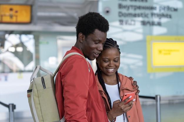 Amorevole coppia di viaggiatori neri in attesa del volo nel terminal dell'aeroporto guardando il telefono