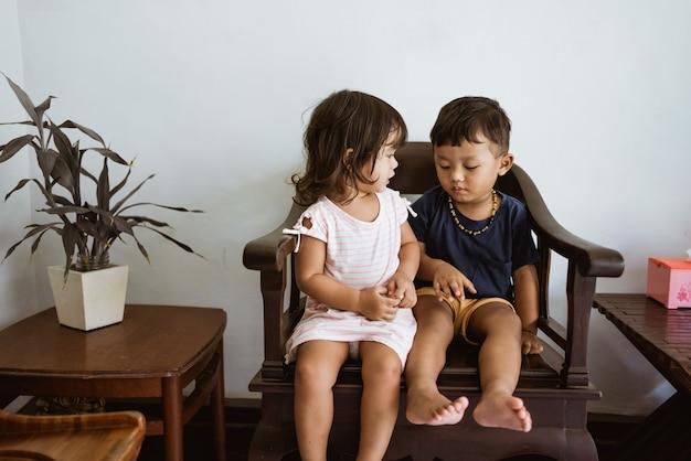 Amorevole fratello e sorellina che si abbracciano seduti su una sedia