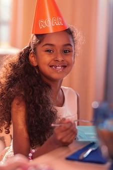 Torta amorevole. ragazza rilassata allegra che indossa il cappello del partito e sorridente mentre mangia la torta saporita