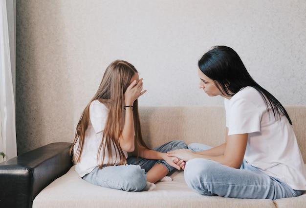 Una madre amorevole e premurosa le tiene la mano e calma la sua angosciata e piangente figlia.