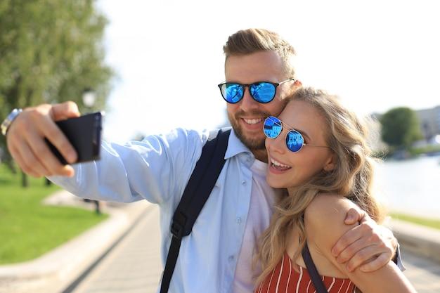 Amorevole coppia felice allegra prendendo selfie in città.